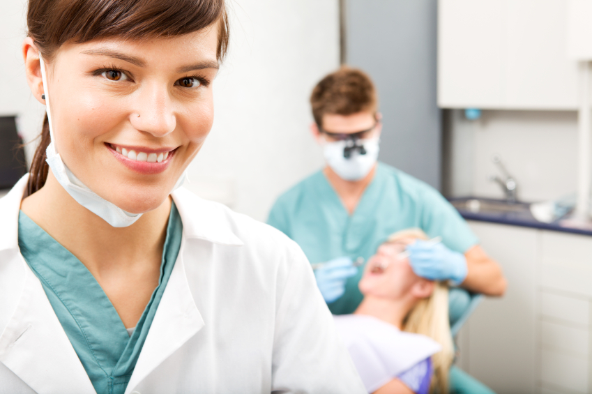 Smiling dental assistant with dentist and patient in background local dental SEO