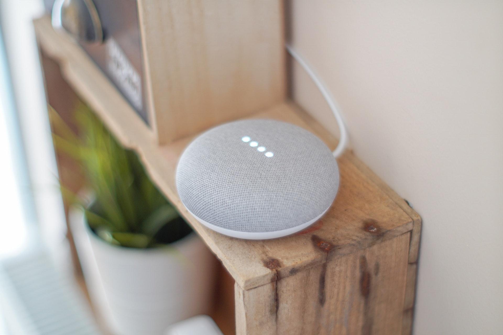 round grey google home speaker on brown board